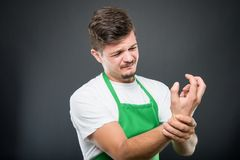 Portrait of supermarket employer holding wrist like hurting. Portrait of supermarket employer holding elbow like hurting on black background Stock Photo