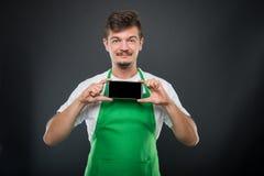 Portrait supermarket employer holding smartphone and smiling Stock Image