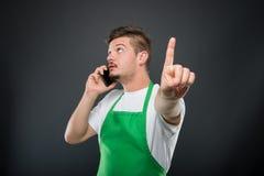 Portrait supermarket employer talking at smartphone gesturing ho Royalty Free Stock Images