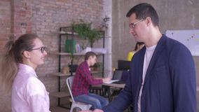 Portrait of supervisor and new employee shake hands on background of office workers at table with computers stock video