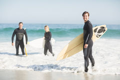 Portrait of surfer friends with surfboard standing on the beach. On a sunny day Stock Images