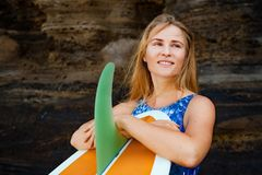 Portrait of surfer girl with surfboard on sea cliff background. Sporty girl in bikini with surfboard stand by black cliff on beach. Surfer woman look at sea surf stock photos