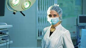 Portrait of a surgeon doctor, after surgery. A tired female surgeon looks into the camera and takes off a surgical mask, she smiles stock video