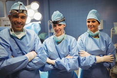 Portrait of surgeon and nurses standing with arms crossed in operation room Stock Image