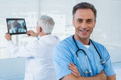 Portrait of surgeon standing with arms crossed. And doctor examining x-ray in background Royalty Free Stock Photography
