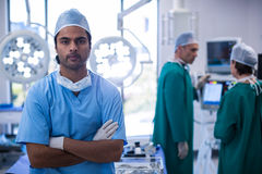 Portrait of surgeon standing with arms crossed in operation room. At hospital Stock Image