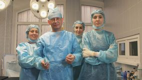 Portrait of a surgeon team after a successful operation. The surgeon crosses his arms with a team of nurses in the operating room Stock Photo