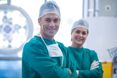 Portrait of surgeons standing with arms crossed in operation room Royalty Free Stock Photos