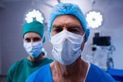Portrait of surgeons wearing surgical mask in operation theater. Of hospital Stock Image