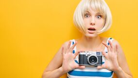 Portrait of a surprise girl with a camera in hand on a yellow background. Isolated studio
