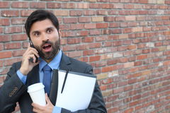 Portrait of a surprised amazed man in eyeglasses talking on mobile phone isolated on brick wall outdoors urban background Royalty Free Stock Image