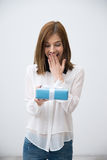 Portrait of a surprised attractive woman holding gift Stock Images