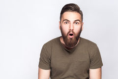 Portrait of surprised bearded man with dark green t shirt against light gray background. Studio shot Royalty Free Stock Photography