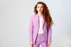 Portrait of surprised beautiful business woman with red - brown hair and makeup in pink suit. looking at camera, Royalty Free Stock Image