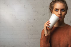 Portrait of surprised beautiful girl with a cup of coffee in hand. Eyes wide open Stock Photography