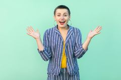 Portrait of surprised beautiful short hair young stylish woman in casual striped suit standing, raised arms, looking at camera royalty free stock photography