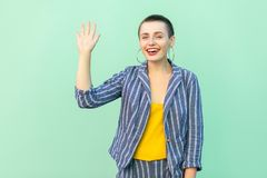 Portrait of surprised beautiful short hair young woman in casual striped suit standing, toothy smile, waving hands and looking at royalty free stock images