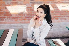 Portrait of surprised beautiful woman with dark pony tail sitting at cafe chatting with her best friend over smartphone gossiping stock images