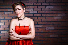 Portrait of surprised beautiful woman in a red dress. Against a brick wall Stock Photography