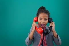 Portrait of surprised businesswoman talking land line phones. Against blue background Stock Photos