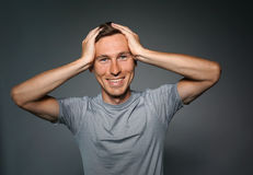 Portrait of a surprised caucasian man with hands on head. Stock Photo