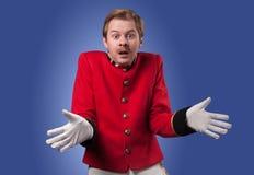 Portrait of  surprised concierge (porter). Portrait of surprised concierge (porter) in a red jacket on a gradient blue background Royalty Free Stock Photos