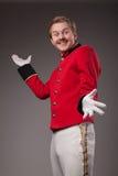 Portrait of  surprised concierge (porter). Portrait of surprised concierge (porter) in a red jacket on a gradient dark background Stock Image