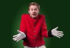 Portrait of  surprised concierge (porter). Portrait of surprised concierge (porter) in a red jacket on a gradient green background Stock Photo