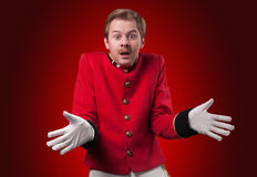 Portrait of  surprised concierge (porter). Portrait of surprised concierge (porter) in a red jacket on a gradient red background Stock Image