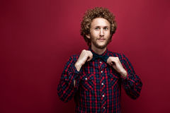 Portrait of surprised curly-haired man in checked shirt and bow-tie on red background. Stock Image