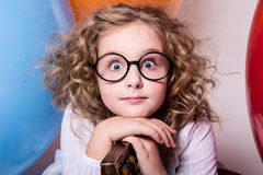 Portrait of surprised curly teen girl in glasses on the backgrou Royalty Free Stock Images