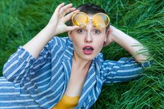 Portrait of surprised cute young woman with short hair in casual blue striped suit lying down on green grass, hoding yellow. Glasses up and looking at camera stock photography