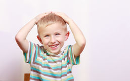 Portrait of surprised emotional blond boy child kid at the table Royalty Free Stock Images