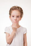 Portrait of surprised excited girl covering her mouth by the hand. Isolated on white background Stock Image