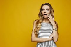 Portrait of surprised excited girl, young beautiful model woman, stands with open mouth and touching her face looks aside and posi royalty free stock image