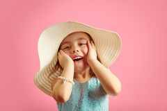 Portrait of surprised girl with open moutn, wears beach hat and beautiful blue dress, expresses joy and happiness royalty free stock photos