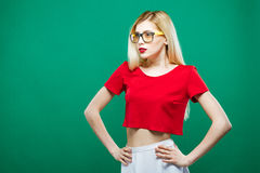 Portrait of Surprised Girl Wearing Short Red Top and Eyeglasses. Sensual Pretty Blonde with Long Hair is Posing on Green Royalty Free Stock Photo