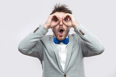 Portrait of surprised handsome bearded man in casual grey suit, blue bow tie standing with binoculars gesture hand on eyes and. Looking at camera. indoor studio stock photography