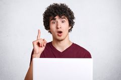Portrait of surprised hipster guy keeps jaw dropped and fore finger raised, uses laptop computer, gets brilliant idea for creating. New article, isolated over Stock Photos