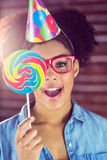 Portrait of a surprised hipster hiding herself behind a lollipop Royalty Free Stock Image