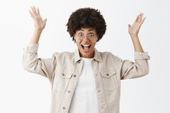 Portrait of surprised and impressed excited african american woman in glasses and beige shirt raising palms high in. Amazement gesture smiling broadly from royalty free stock images