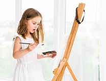 Portrait of surprised little girl painting a picture Stock Image