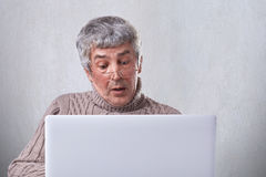 A portrait of surprised mature man in glasses having puzzled expresion while looking into the screen of a laptop. A senior man sho Royalty Free Stock Images