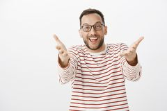 Portrait of surprised pleased adult man seeing friend and pulling hands towards camera as if wanting to cuddle, greeting. Family member friendly, iviting to stock photo