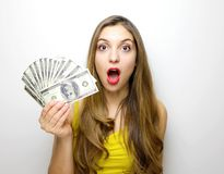 Portrait of a surprised pretty girl looking at camera with money banknotes in her hand isolated over white background royalty free stock image