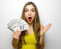 Portrait of a surprised pretty girl looking at camera with money banknotes in her hand isolated over white background royalty free stock photos