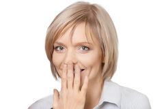 Portrait of surprised pretty young woman. Covering her mouth by the hand and smiling, over white background Stock Photo