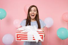 Portrait of surprised pretty young woman in blue dress holding red box with gift present on pastel pink background with stock photos