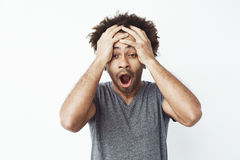 Portrait of surprised and shocked african man with opened mouth finding out he missed a sale or is late to work or Stock Photos