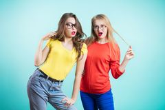 Portrait of the surprised and shocked two women on a blue background royalty free stock photography